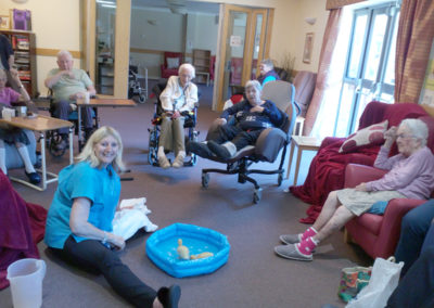 Seated residents in their lounge, watching baby ducks in a small paddling pool
