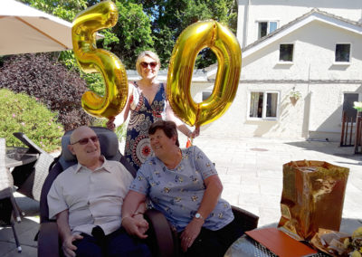 Abbotsleigh Care Home resident and his wife sitting outside in the garden on their 50th anniversary