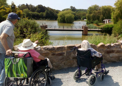 Residents in wheelchairs looking out at a beautiful lake at Hawkhurst Fish Farm