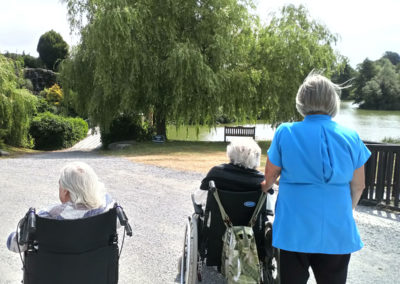 Carers pushing residents in their wheelchairs along a path at Hawkhurst Fish Farm