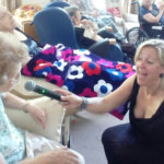 Female singer holding a microphone for a seated resident to sing into