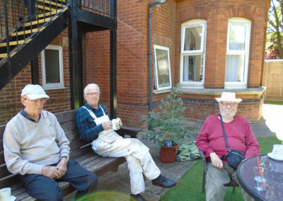 Three gentlemen sitting and relaxing in the garden at Lulworth House Residential Care Home