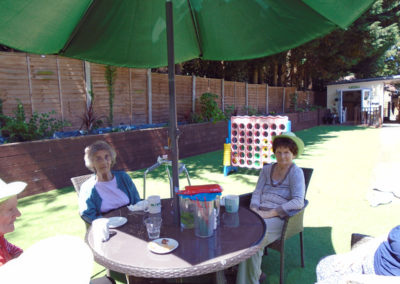 Two ladies sitting and relaxing in the garden at Lulworth House Residential Care Home