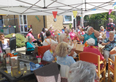 Woodstock Residential Care Home residents and family members sat outside singing and dancing in their chairs to an Elvis singer