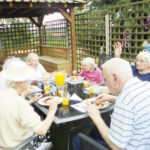Residents at The Old Downs Residential Care Home enjoying eating lunch together outside in the garden