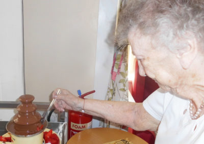 Woodstock lady dipping a strawberry into a chocolate fountain