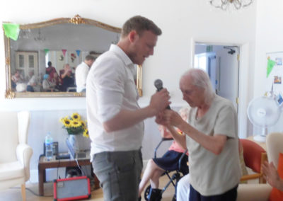 Curtis Skinner singing and holding hands with a resident at Woodstock