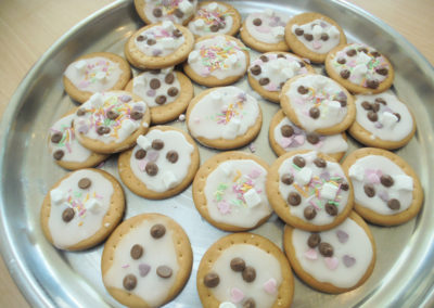 A silver plate of cookies decorated by residents at The Old Downs Residential Care Home with icing and sweets