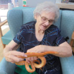 One of the ladies at The Old Downs Residential Care Home petting a snake from Zoolab