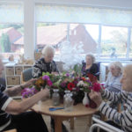 A group of residents at The Old Downs flower arranging around a table in the conservatory