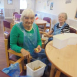 Two lady residents of The Old Downs Residential Care Home peeling potatoes for the Sunday roast