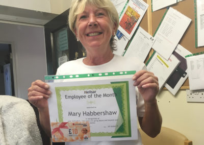 Employee of the month Mary Habbershaw holding up a certificate and shopping vouchers