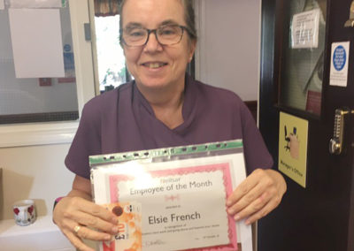 Employee of the month Elsie French holding up a certificate and shopping vouchers