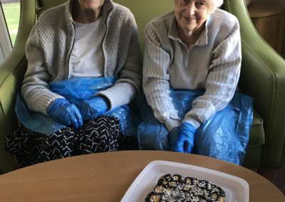 Two lady residents at Lulworth House showing off their decorated chocolate cake