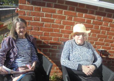 Two residents enjoying the sun in the garden at the Old Downs Residential Care Home