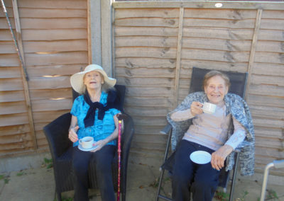 Two residents enjoying a cup of tea in the garden at the Old Downs Residential Care Home