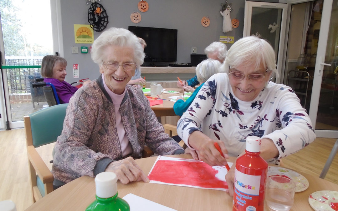 Two lady residents from The Old Downs Residential Care Home making poppy pictures for Remembrance Sunday