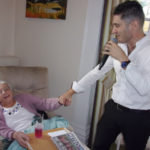 Singer Kevin Walsh, holding hands with a resident as he sings to her