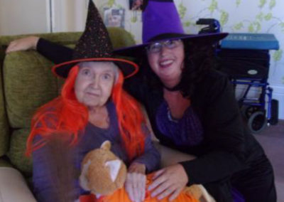Loose Valley staff member with a resident wearing colourful witch costumes