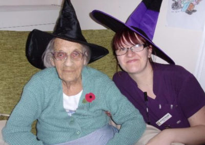 Loose Valley staff member with a resident wearing black and purple witch hats