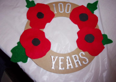 A giant handmade poppy wreath with 100 years in silver