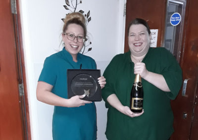 Two Care Staff at Meyer House with their winning trophy and a bottle of Paul Langier Champagne
