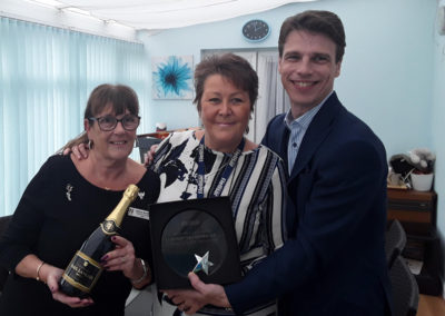 Gill Redsell (Meyer House Manager, Viv Stead (Recreation & Well-Being Manager), Martin Barrett (Managing Director) posing with the Champion Fundraising trophy and champagne