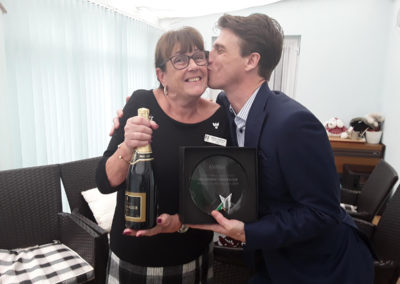 Martin Barrett (Managing Director) kisses Gill Redsell (Meyer House Manager) as he congratulates her with the trophy win