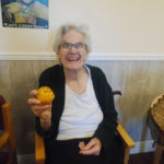 Lady resident at The Old Downs Residential Care Home with a decorated orange for Halloween