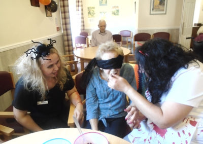 Residents and staff at The Old Downs Residential Care Home playing Halloween food tasting games