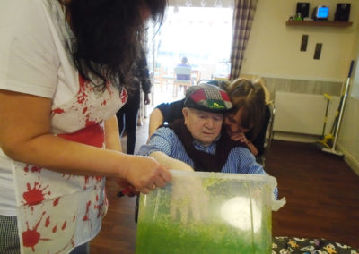 Residents and staff at The Old Downs Residential Care Home playing Halloween What can you find in the gloop game