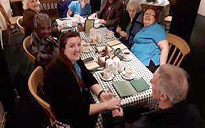 Abbotsleigh Care Home residents and staff sitting around a table in a tea room