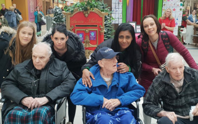 Three Lukestone Care Home residents in wheelchairs with staff, posing for a photo at the shopping Mall