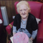 Resident Joan at The Old Downs Residential Care Home with her pink butterfly birthday cake