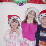 Three young children in Santa hats at the Loose Valley Christmas party