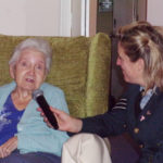 A Loose Valley Care Home female resident singing into a microphone with a wartime singer