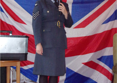 A female singer, dressed in an Airforce uniform, singing in front of a Union Jack flag
