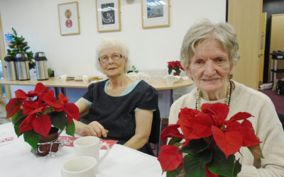 Two Lulworth House Residential Care Home ladies sitting with poinsettia plants, at a trip to Invicta School