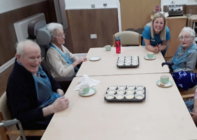 Abbotsleigh Care Home residents sat around a table preparing cupcakes