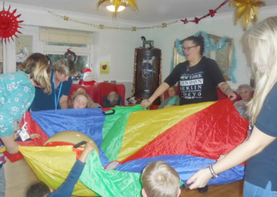 Young children from Rodmersham Nursery playing parachute games with residents from Woodstock Residential Care Home
