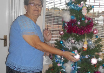 A resident at Woodstock decorating a Christmas Tree on the upstairs landing