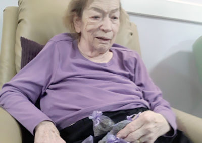 Abbotsleigh Care Home lady resident sitting in a chair holding some bags of lavender