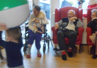 Young children from Rodmersham Nursery playing ball catch with residents from Woodstock Residential Care Home