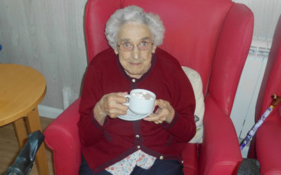 Woodstock Residential Care Home lady resident sitting in a chair, enjoying a cup of hot chocolate