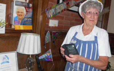 The Assistant Chef at Woodstock Residential Care Home holding her birthday plaque on her 80th birthday