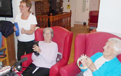 Two ladies from Woodstock Residential Care Home seated with tambourines, during an exercise class