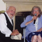 An entertainer and Loose Valley resident together, with the resident singing with a microphone