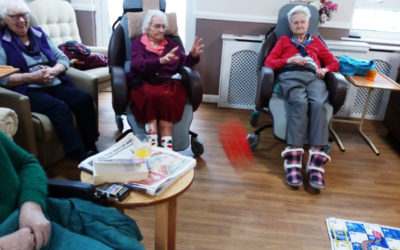 Meyer House Care Home residents seated around a floor snakes and ladders game, with one lady throwing a large dice