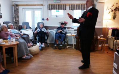 Residents at Meyer House Care Home watching a magician perform in their lounge