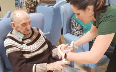 Lukestone Care Home resident and member of staff from Wild Science holding a snake